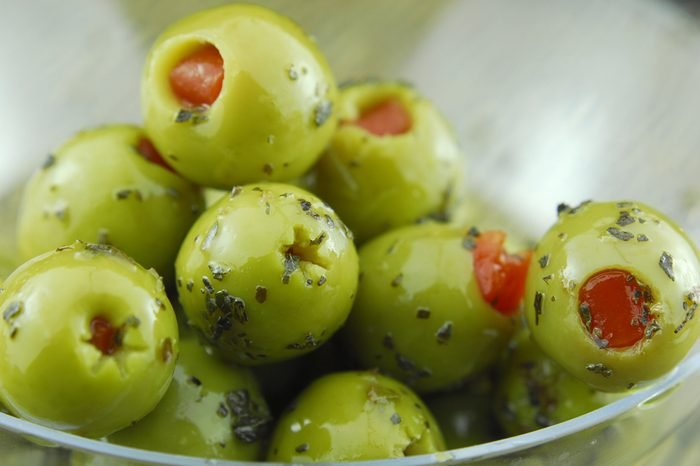 green olive oil stuffed with pimento , spiced with basil and olive oil