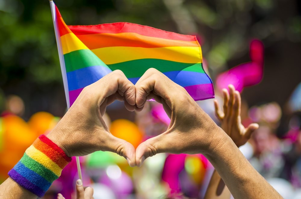 Supporting hands make heart sign and wave in front of a rainbow flag flying on the sidelines of a summer gay pride parade