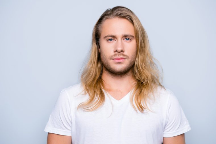 Portrait of handsome young serious confident young guy with blonde long hair in white tshirt, isolated on grey background