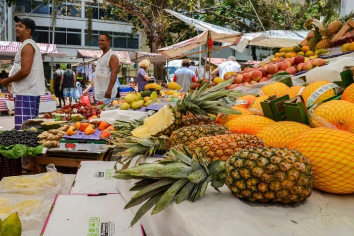 Rio de Janeiro, Brazil - Dec 15, 2017: Assortment of fresh tropical fruits at a street market in Rio de Janeiro, Brazil - focus on pineapples