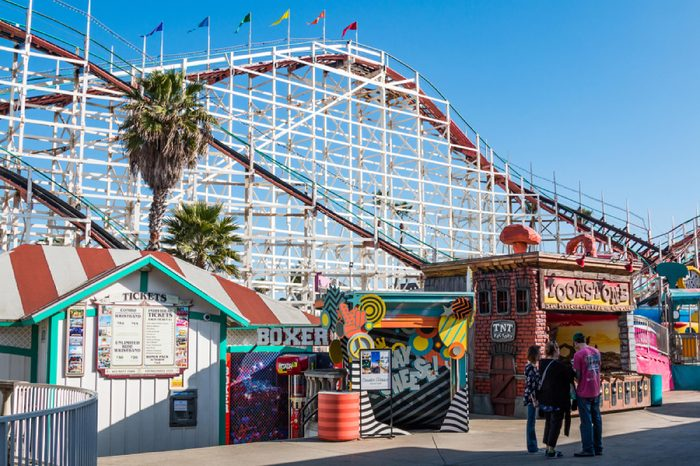SAN DIEGO, CALIFORNIA - FEBRUARY 9, 2018: People walk on the midway at Belmont Park, an amusement park built in 1925 on the Mission Beach boardwalk with the iconic Giant Dipper roller coaster.