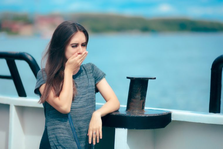 Sea sick woman suffering motion sickness while on boat. Suffering girl traveling on water and feeling fearful and unwell