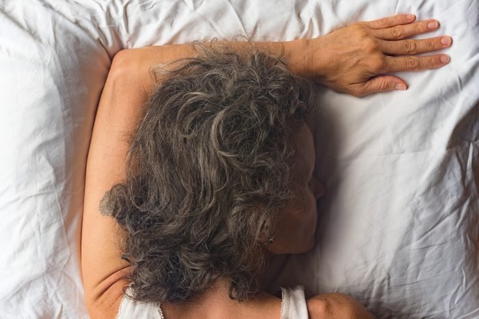 High angle close up view of middle aged woman sleeping face down on pillow with arm overhead (selective focus)