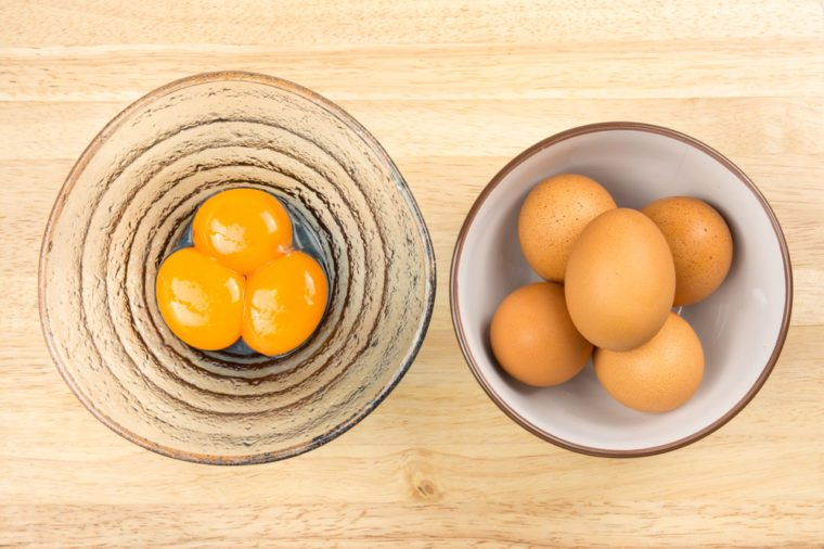 Raw eggs in ceramic bowl and egg yolks in glasses bowl on wooden table, top view