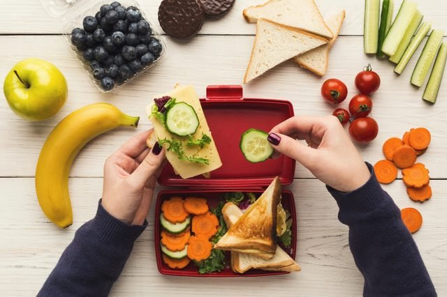 Preparing healthy vegetarian snacks on white rustic wood. Female hands making sandwiches and putting into take away plastic lunch box, top view. Eating right, picnic and food storage concept
