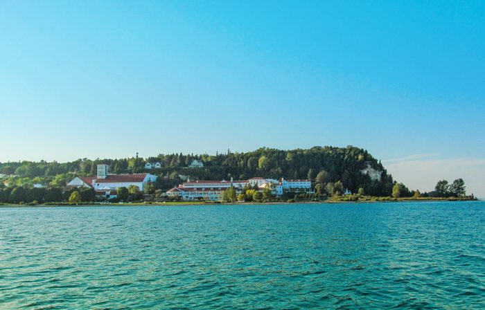 Mackinac Island in Northern Michigan, USA. Summer landscape with houses and trees on the shore, water and blue sky.