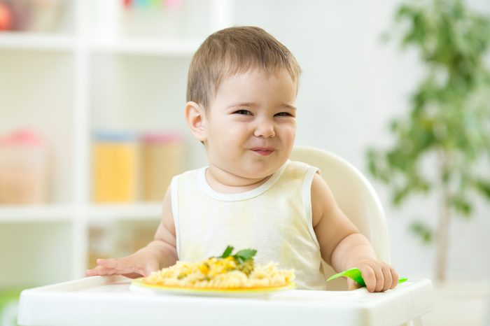 funny baby boy eating healthy food in nursery