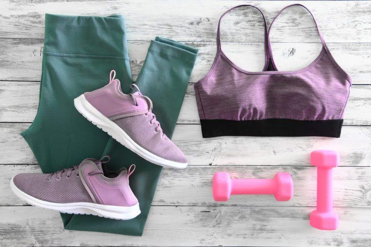 Womens active clothes (leggings, bra) footwear (sneakers) and equipment (pink dumbbells). Active lifestyle concept, Flat lay