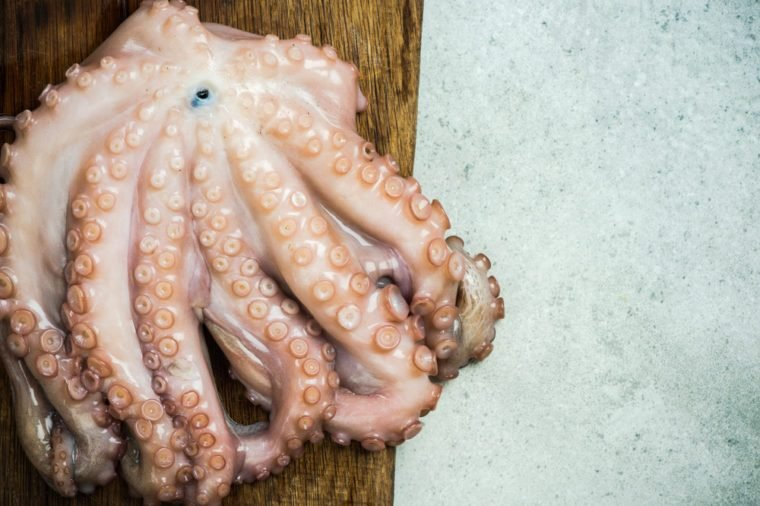 Whole fresh octopus on cutting board.