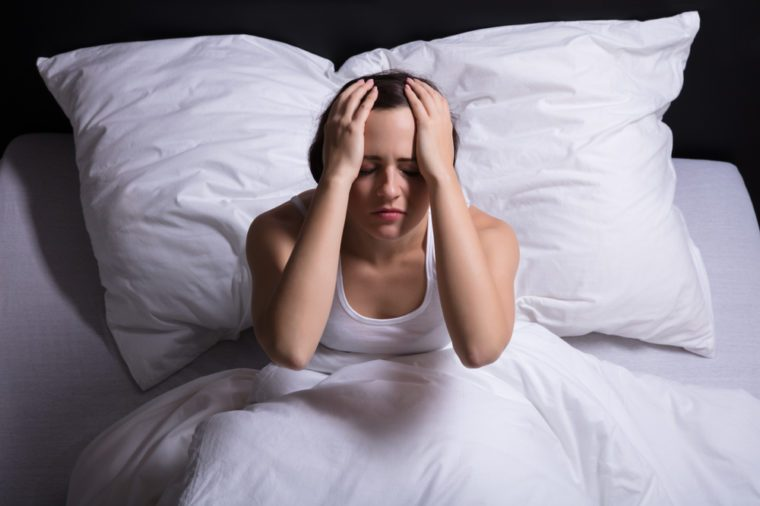 Young Woman Sitting On Bed Suffering From Headache