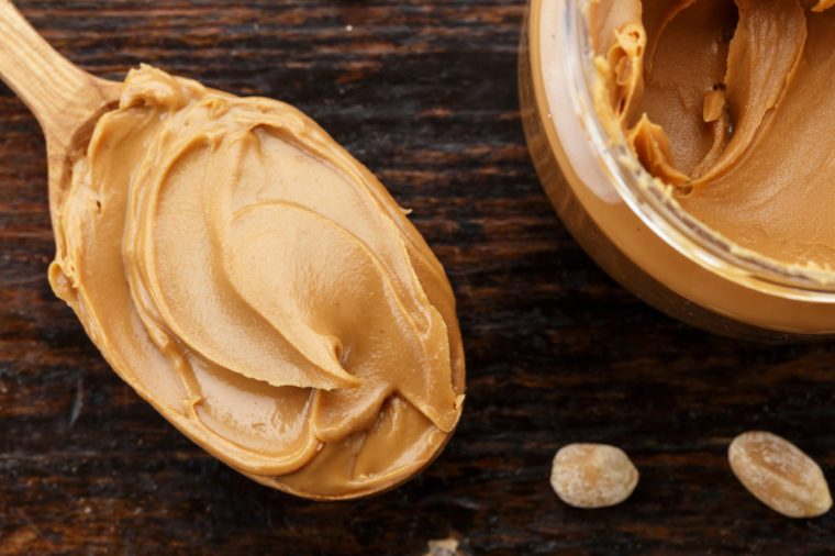 natural organic peanut butter in a spoon isolated, on a wooden background, top view