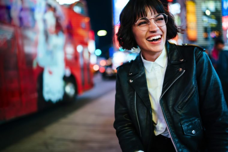 Pretty positive young woman with short haircut laughing in urban setting with night lights enjoying leisure time in New York.Happy hipster in stylish wear and eyewear having fun on megapolis street