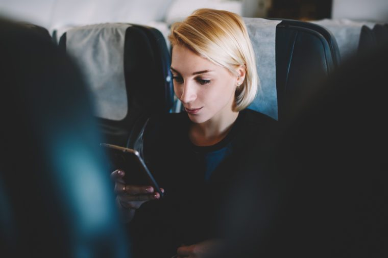 Beautiful bonde female passenger checking email on smartphone communicating online with wireless internet connection during business trip on plane sitting in first class on comfortable seat