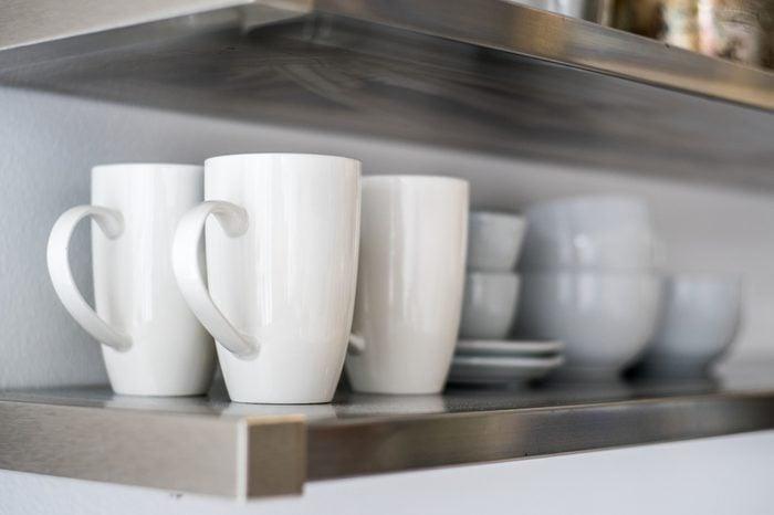 Ceramic bowls and mugs on kitchen shelf