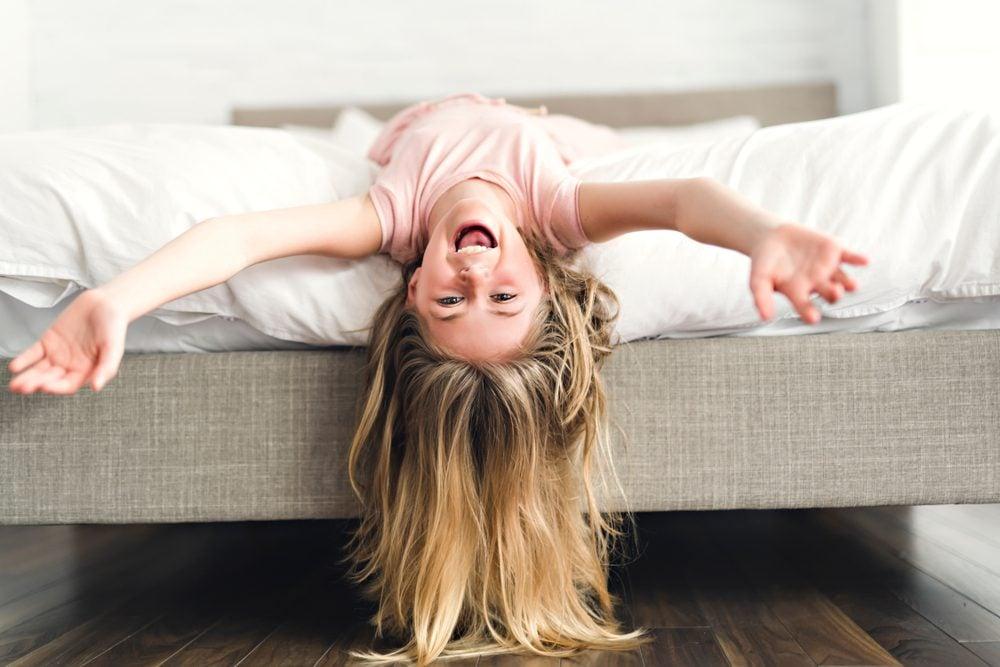Cute little blonde girl in her pajamas on bedroom