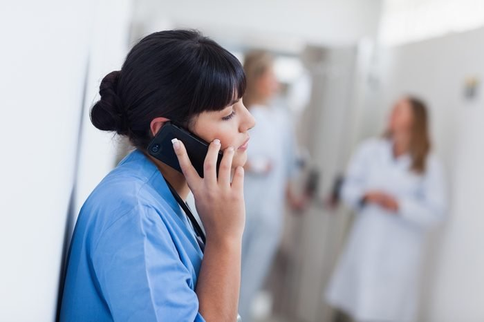 Nurse holding a mobile phone in hospital ward