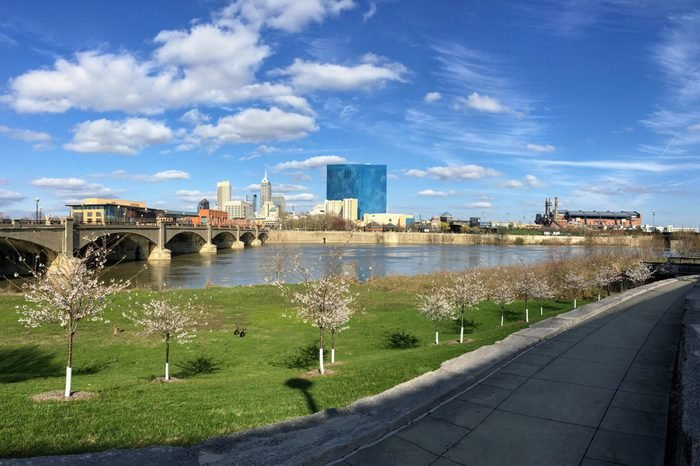 Downtown City Skyline Indianapolis Indiana White River in spring with blooming trees and vegetation, pedestrian bridges and ruins.