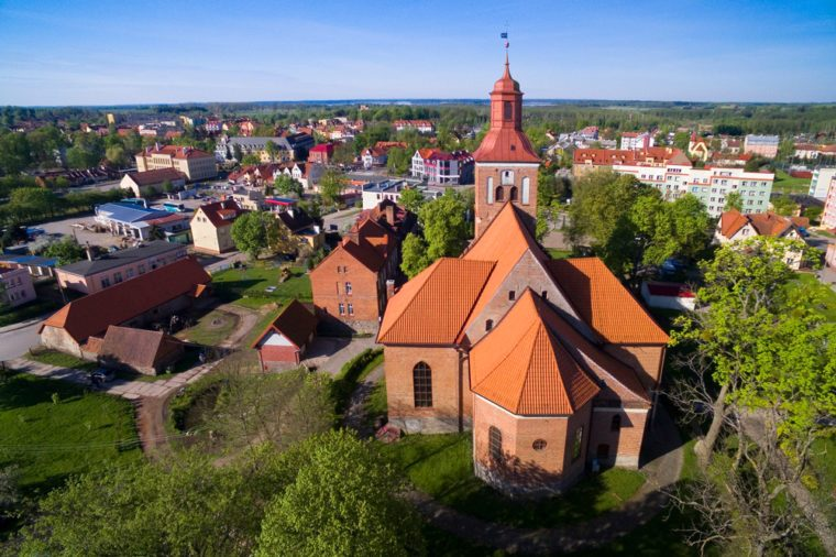 Aerial view of Wegorzewo town, Poland (former Angerburg, East Prussia). Gothic style St. Peter and St. Paul's Church on the right
