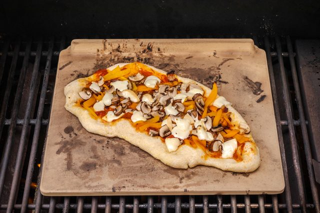 Pizza cooked on a pizza stone over a hot grill. Pizza is topped with roasted sweet peppers, mushrooms and smoked mozzarella.