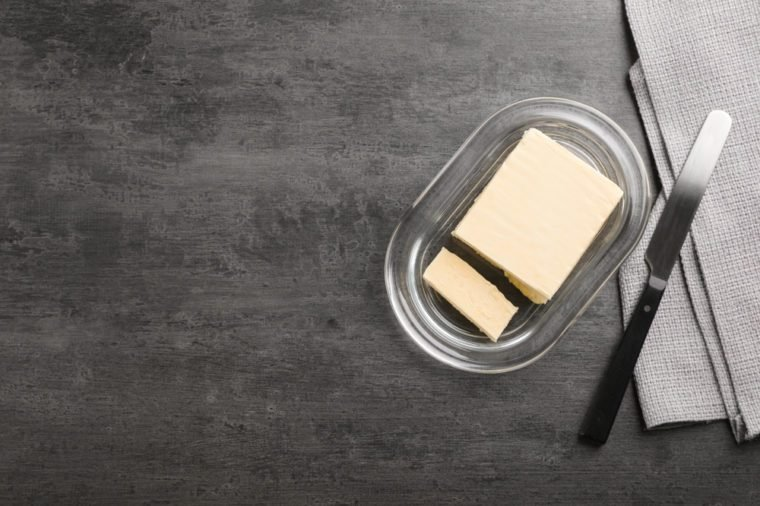 Plate with tasty fresh butter and knife on table, top view