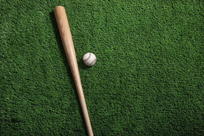 Baseball bat and ball on green turf background