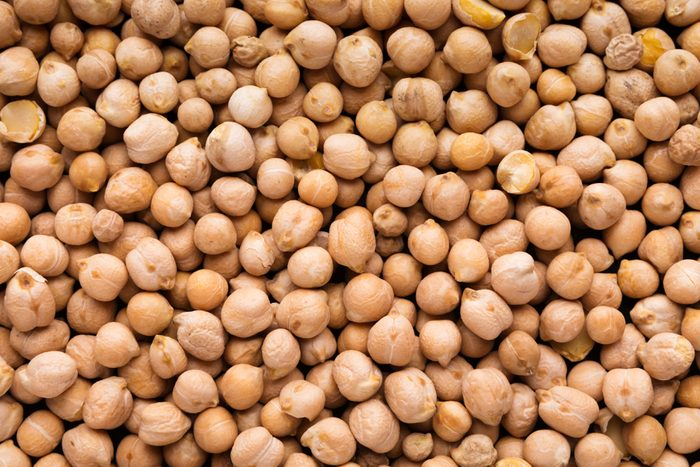 Food background from raw uncooked chickpeas, top view, closeup