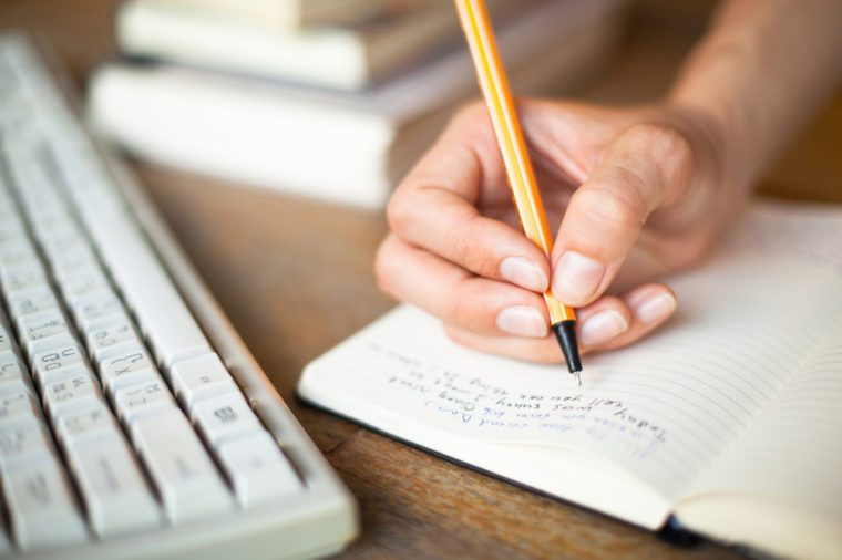 Photo of hands writes a pen in a notebook, computer keyboard and a stack of books in background
