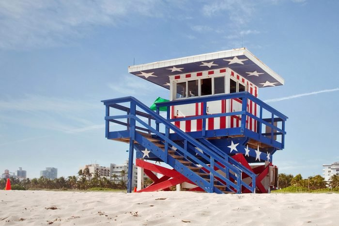 Miami Beach Florida, lifeguard house in a typical colorful Art Deco style,painted in the American flag colors on a summer day, with blue sky and Ocean in the background. Famous travel location.