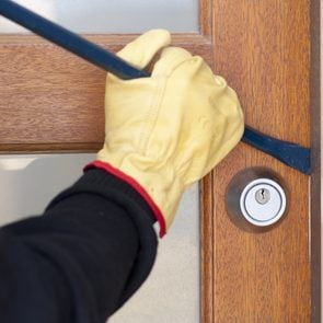 Burglar, thief  with gloves, holding crowbar breaking into home, unlock door, copy space.