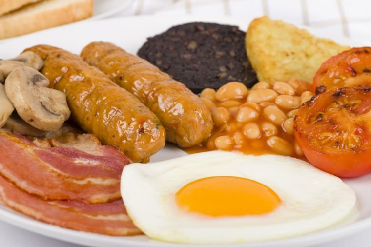 Full English Breakfast - Traditional English fry-up with egg, bacon, mushrooms, tomatoes, sausages, black pudding, hash browns and baked beans. Served with slices of toast.