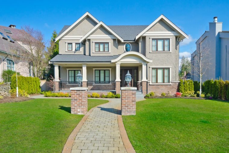 Big custom made luxury house with long doorway and nicely trimmed front yard in the suburbs of Vancouver, Canada.