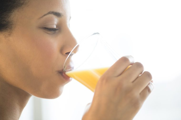 Young woman drinking glass of orange juice at gym