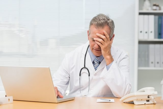 Stressed doctor sitting at his desk in his office at the hospital