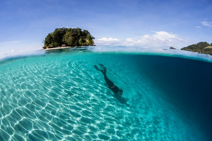A snorkeler does some free diving along a sandy slope in the Solomon Islands. This country offers incredibly diverse marine habitats, great scuba diving, and fantastic snorkeling.