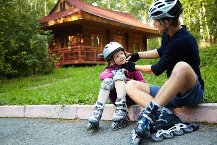 portrait of a sports dad and daughter in a helmet. Dad with his little daughter on the skates