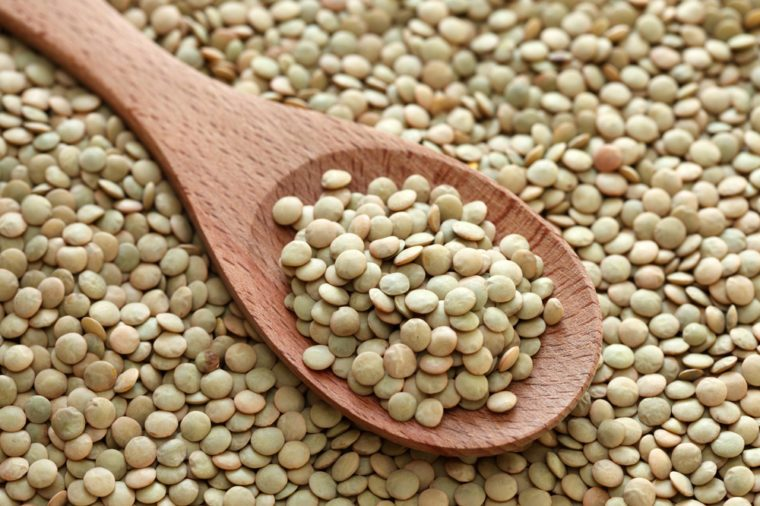Green lentils in a wooden spoon on green lentils background. Close-up.