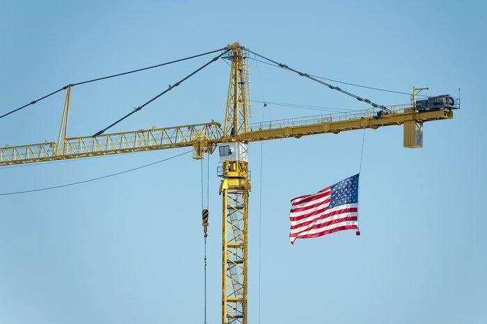 yellow industrial big crane with american flag