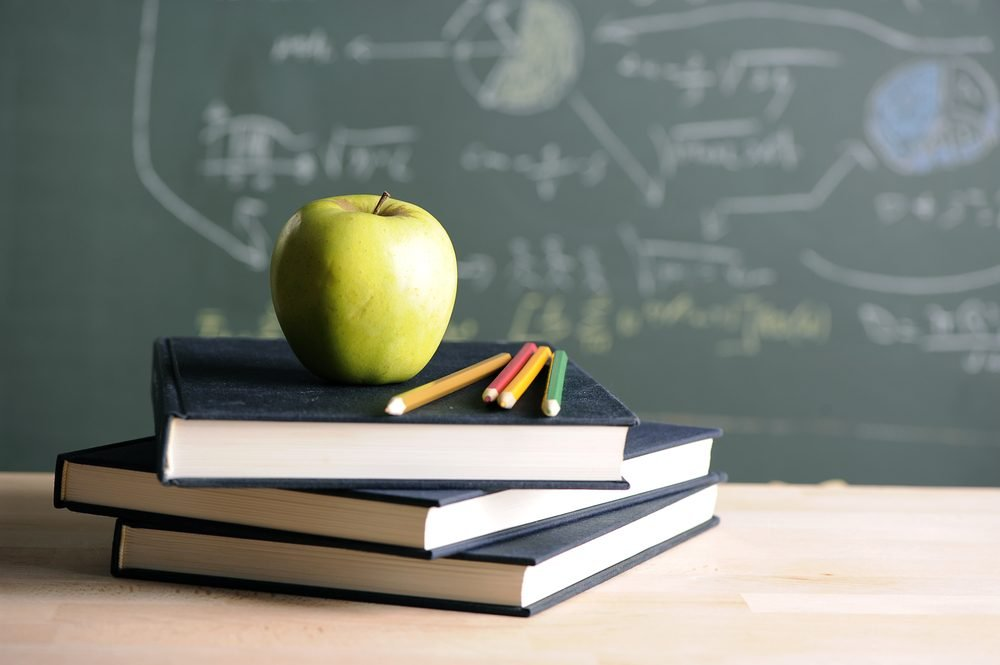 A school teacher's desk with stack of exercise books colored pencils and green apple. A green blackboard