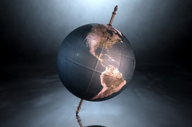 A vintage world globe tilted and standing on a central axis on an isolated spotlit dark background