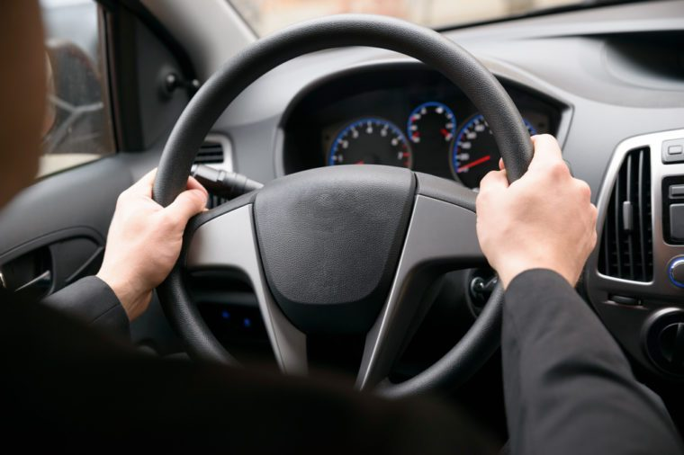 Close-up Of A Man Hands Holding Steering Wheel While Driving Car