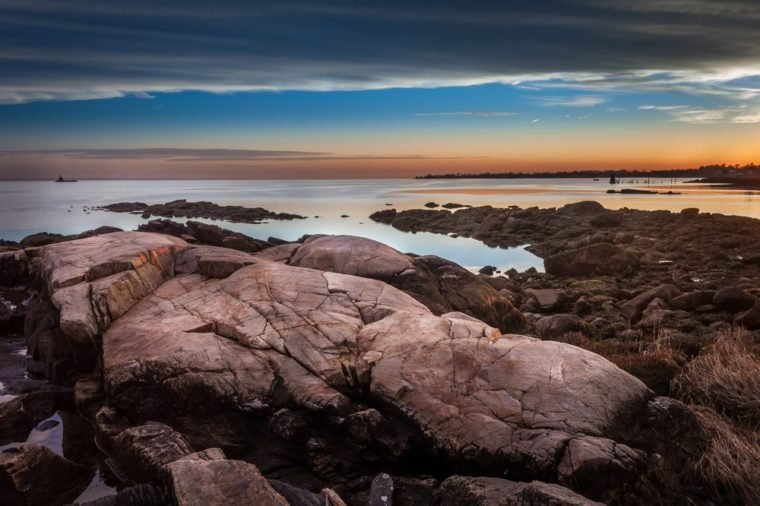 Boulders On The Shore At Sunset With Lighthouse In The Distance