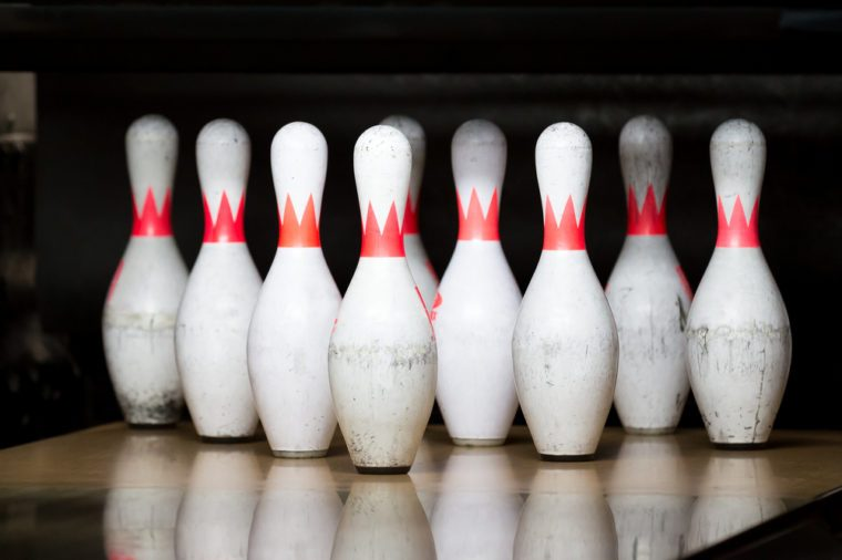 white with red stripe pins in of triangle at bowling alley