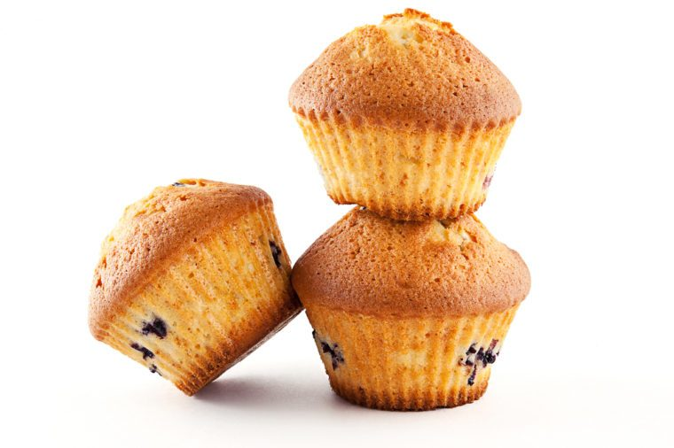Tasty muffins with blueberry on white background