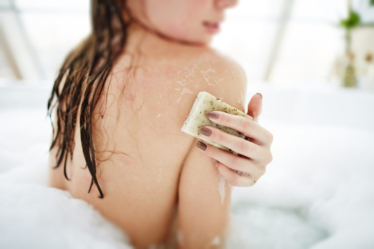 Young woman exfoliating her skin with soap