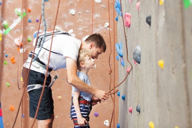 young father preparing his little son for climbing in indoor gym