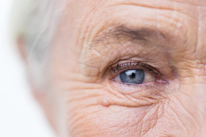 age, vision and old people concept - close up of senior woman face and eye