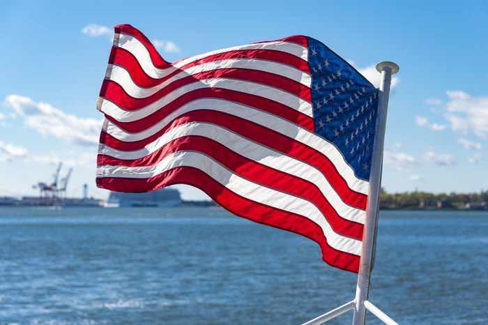 United States of America flag flying or waving in boat or cruise in the Hudson River. Beautiful symbol of freedom in New York city.
