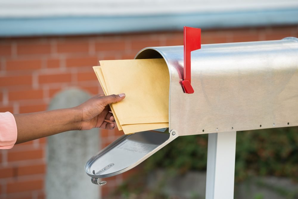 Close-up Of Person's Hand Putting Letters In Mailbox