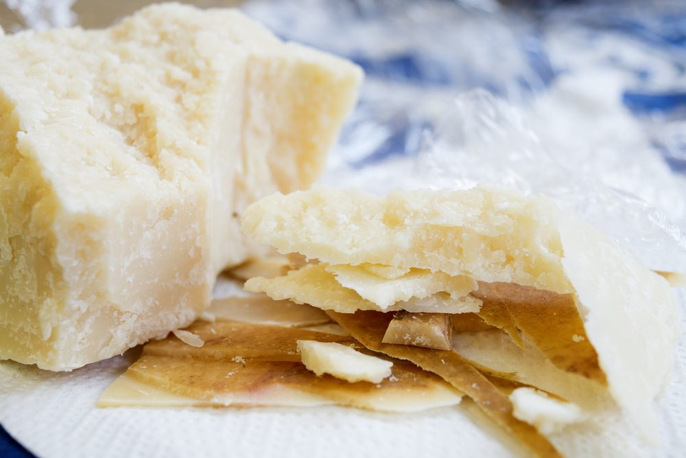 chunks and rind of parmigiano cheese with near a big piece of heart