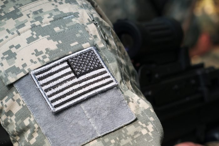 US Army uniform element - sleeve patch with flag and machine gun on the background